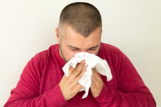 Jonge man met zakdoek en niezen op witte achtergrond