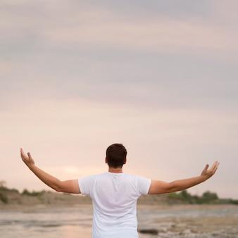 Jonge man met zijn armen in de lucht