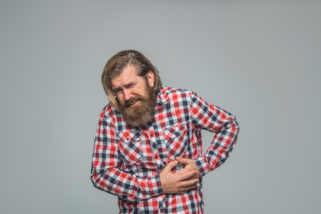 Jonge man met zijn buik bebaarde man voelt pijn maagpijn probleem ziekte portret concept