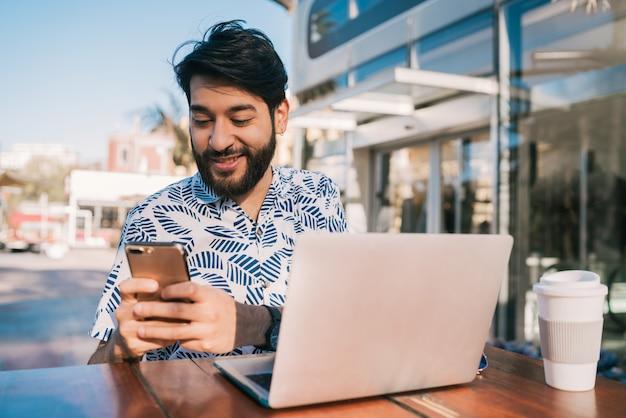 Jonge man met zijn laptop en mobiele telefoon