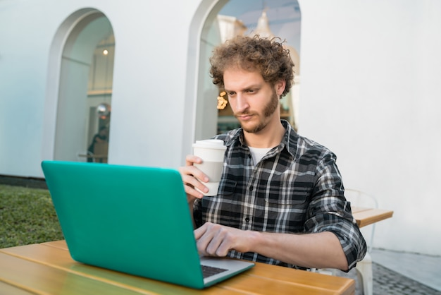 Jonge man met zijn laptop in een koffieshop.
