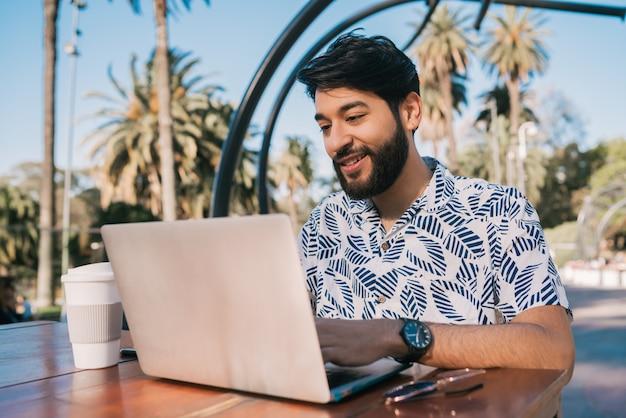 Jonge man met zijn laptop in een koffieshop