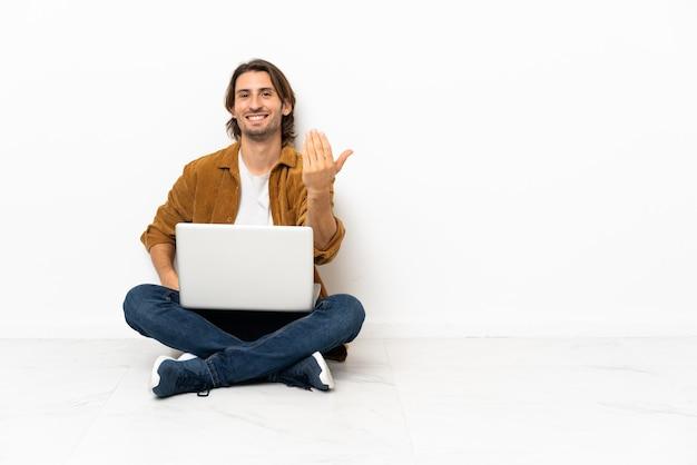 Jonge man met zijn laptop zittend op de vloer die uitnodigt om met de hand te komen. blij dat je gekomen bent