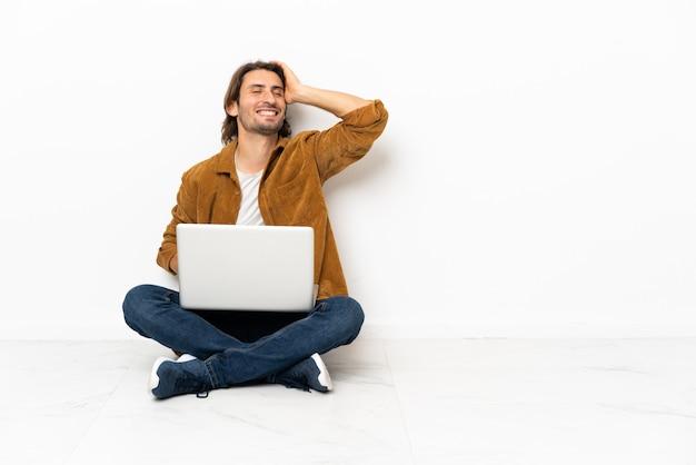 Jonge man met zijn laptop zittend op de vloer heeft iets gerealiseerd en de oplossing voor ogen