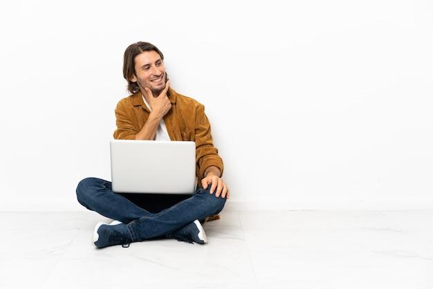 Jonge man met zijn laptop zittend op de vloer op zoek naar kant