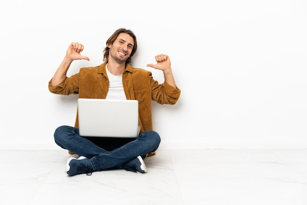 Jonge man met zijn laptop zittend op de vloer trots en zelfvoldaan