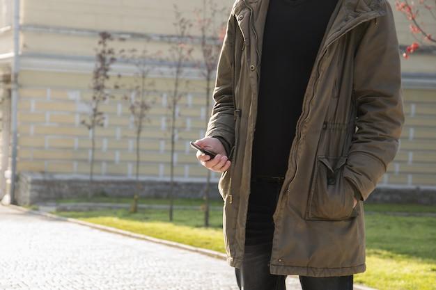 Jonge man met zijn mobiele telefoon in de straat