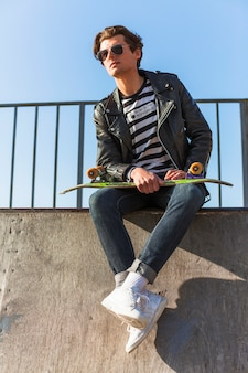 Jonge man met zijn skateboarden op de skatepark