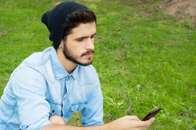 Jonge man met zijn telefoon. buitenshuis.
