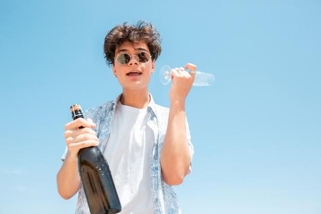 Jonge man met zonnebril en champagne fles