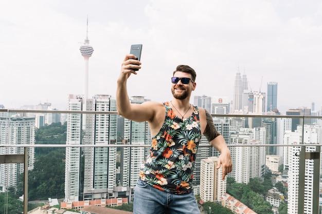 Jonge man met zonnebril en mouwloos t-shirt met bloemenprint die een selfie maakt met de stad