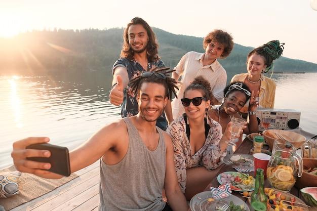 Jonge man mobiele telefoon houden en selfie portret samen met zijn vrienden maken tijdens de lunch op een pier buiten