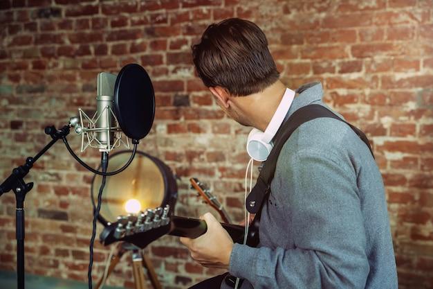 Jonge man muziek opnemen, gitaar spelen en thuis zingen