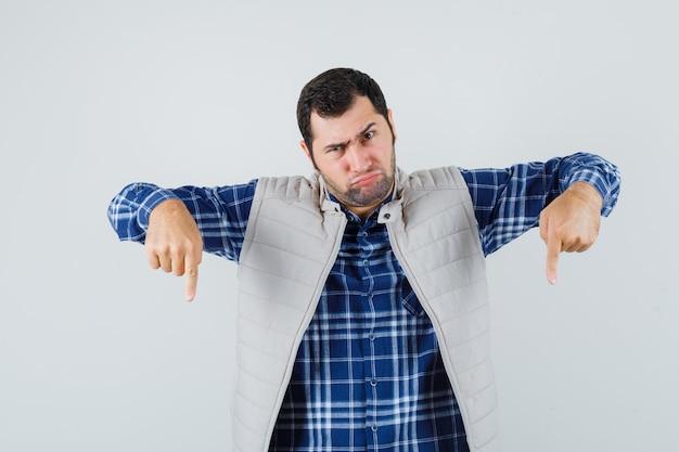 Jonge man naar beneden in shirt, mouwloos jasje en op zoek agressief. vooraanzicht.
