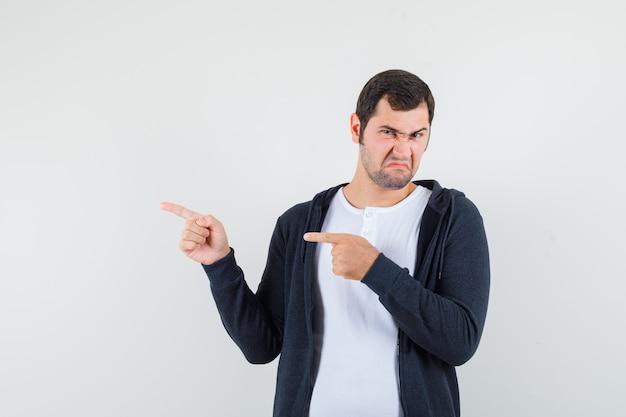 Jonge man naar links wijzend met wijsvingers in wit t-shirt en zwarte hoodie met rits aan de voorkant en kijkt ontevreden, vooraanzicht.
