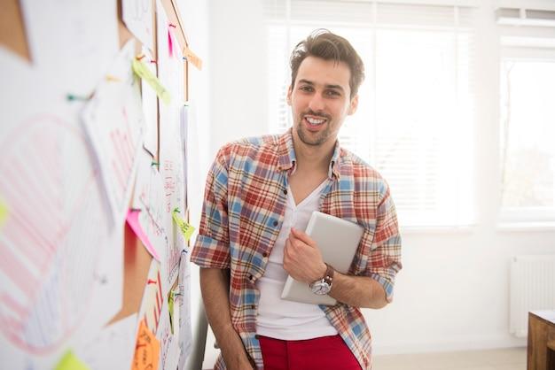 Jonge man naast het bord op kantoor