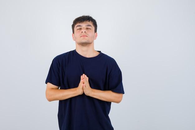 Jonge man namaste gebaar in zwart t-shirt tonen en hoopvol op zoek. vooraanzicht.