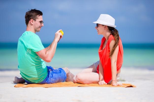 Jonge man neemt foto van zijn vriendin aan de telefoon op het strand