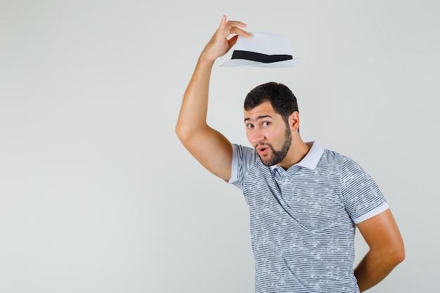 Jonge man neemt zijn hoed af met respect in gestreept t-shirt, hoed en kijkt gefocust. vooraanzicht.
