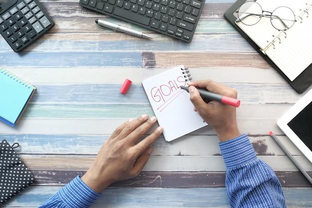 Jonge man nieuwjaar doelen schrijven op kladblok. bovenaanzicht