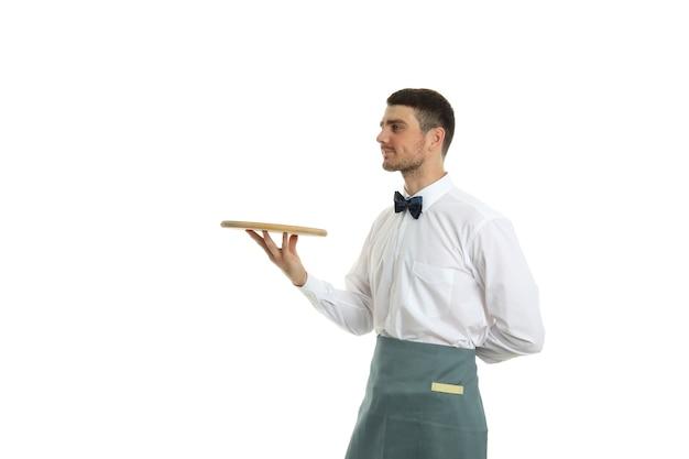 Jonge man ober houdt dienblad, geïsoleerd op een witte achtergrond.