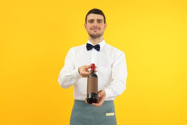 Jonge man ober houdt fles wijn op gele achtergrond.
