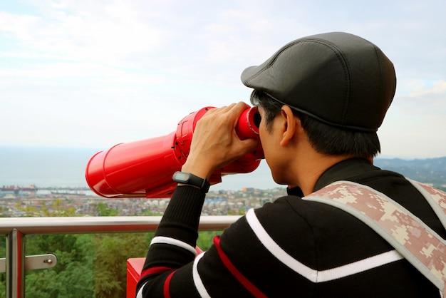 Jonge man observeren luchtfoto stadszicht met verrekijker vanaf het observatiedek
