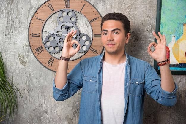 Jonge man ok gebaar tonen en poseren op marmeren achtergrond. hoge kwaliteit foto