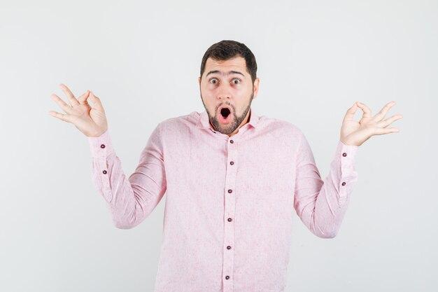Jonge man ok teken in roze shirt tonen en vraagt zich af
