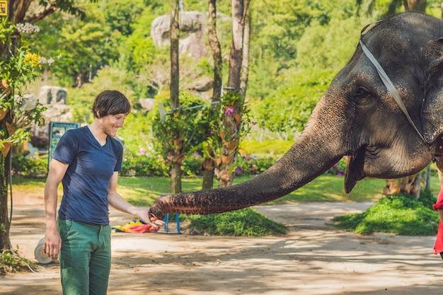 Jonge man olifant voederen in de dierentuin