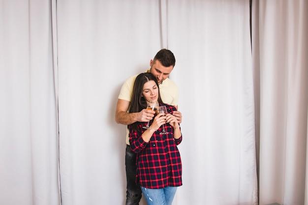 Jonge man omarmen zijn vriendin bedrijf wijnglazen in de hand