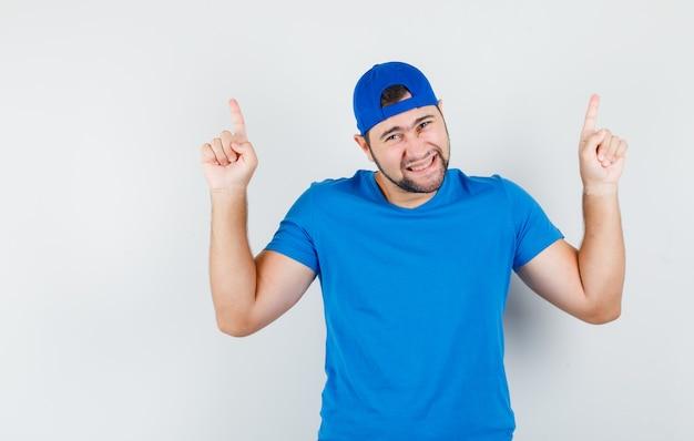 Jonge man omhoog in blauw t-shirt en pet en op zoek gelukkig