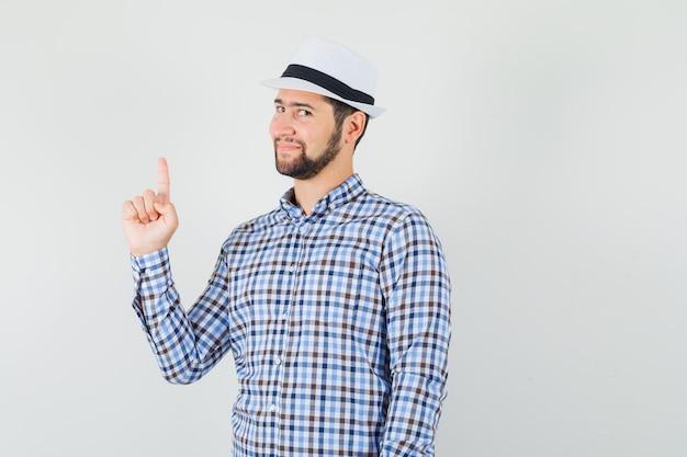 Jonge man omhoog in geruit overhemd, hoed en op zoek verstandig.