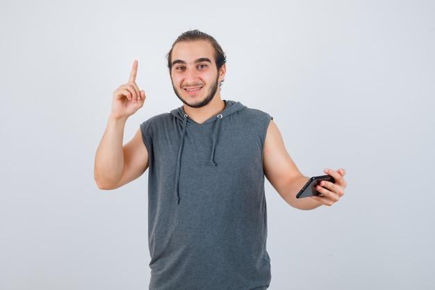 Jonge man omhoog in t-shirt met een kap en kijkt gelukkig, vooraanzicht.