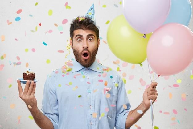 Jonge man omringd door confetti cupcake en ballonnen te houden
