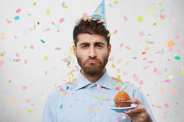 Jonge man omringd door confetti cupcake houden