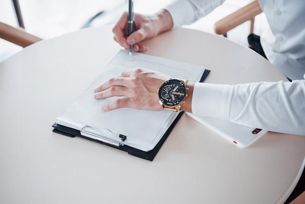 Jonge man ondertekent documenten op kantoor, succesvolle verkoop.