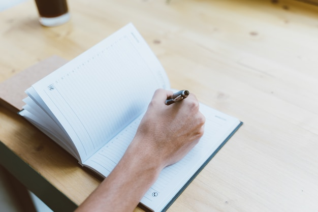 Jonge man, onherkenbaar persoon schrijven van informatie naar kladblok, tiener een schema, dagelijks, to-do lijst