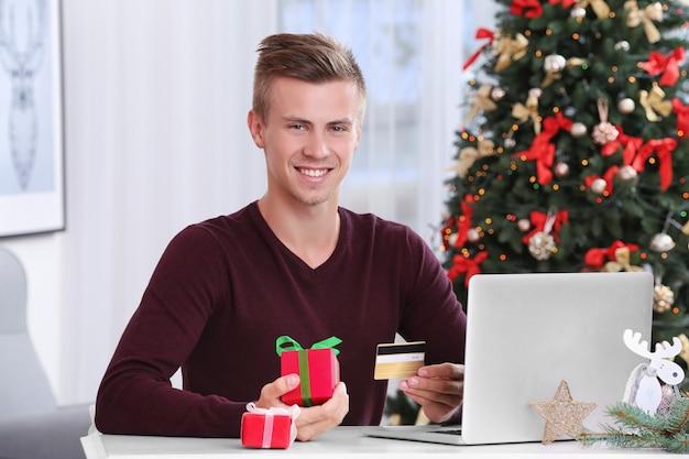 Jonge man online winkelen met creditcard thuis voor kerstmis