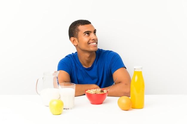 Jonge man ontbijten in een tafel lachen en opzoeken