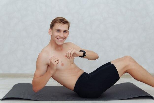Jonge man ontbloot bovenlijf doet pers oefening op fitness mat in kamer thuis. sport concept.