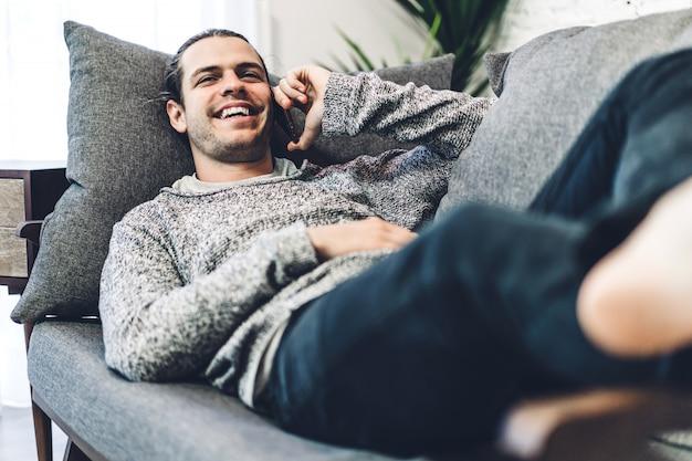 Jonge man ontspannen en het gebruik van smartphone. man sociale apps en werken controleren. communicatie en technologie concept