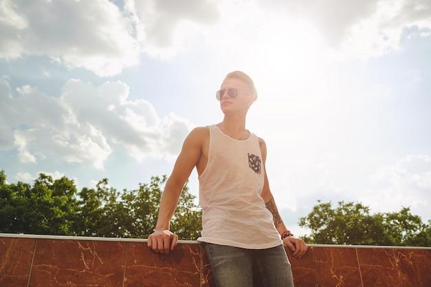 Jonge man ontspannen, genieten van een zonnige dag terwijl je op een bui