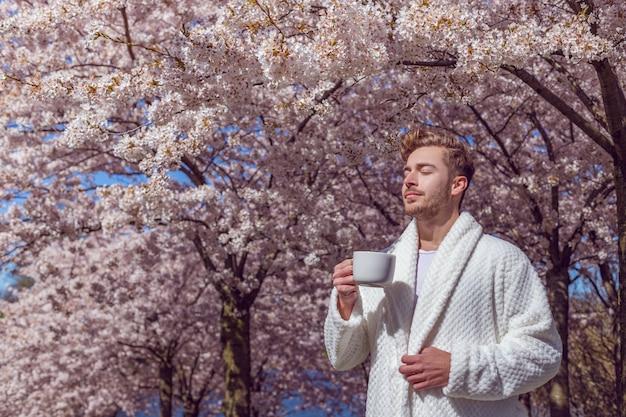 Jonge man ontspannen in de bloeiende lentetuin en koffie drinken uit de beker