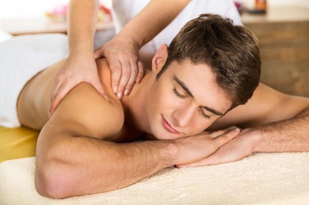 Jonge man ontspannen in de spa, close-up van een man met een rugmassage