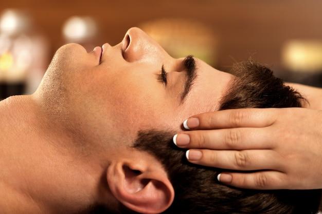 Jonge man ontspannen in de spa, close-up van een man met hoofdmassage