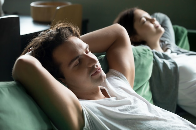 Jonge man ontspannen op comfortabele bank met vriendin thuis