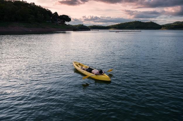 Jonge man ontspannen op gele kano met peddel in het meer 's avonds