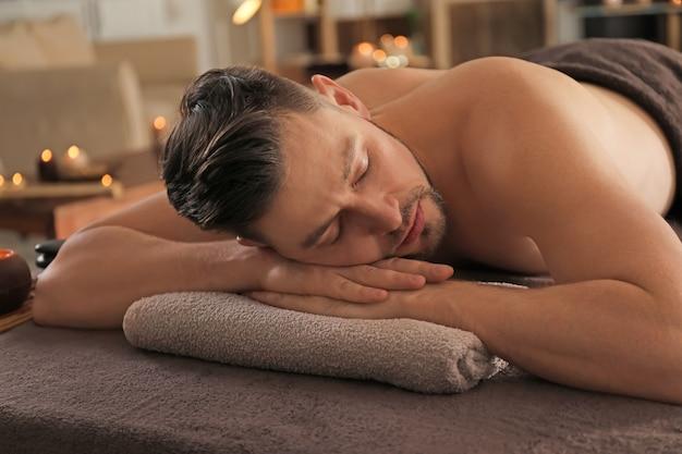 Jonge man ontspannen op massagetafel in spa salon