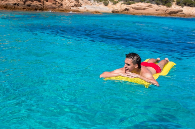 Jonge man ontspannen op opblaasbare matras in de zee